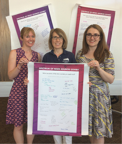 Librarians Elizabeth McMunn-Tetangco, Sara Davidson Squibb, and Lindsay Davis display posters with responses to exhibit questions.