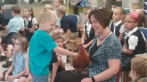 Students learning about biology with Axle Rose, the rooster.