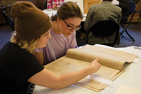 Indiana University students working with materials from the Jonathan Krause Rare Newspaper and Magazine Collection