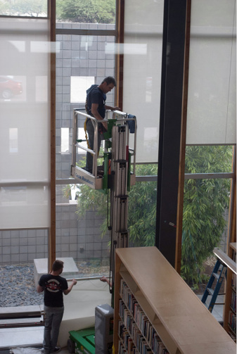 Workers applying UV-filtering film on the Poetry Center's big bank of windows. Photo by Sarah Kortemeier.