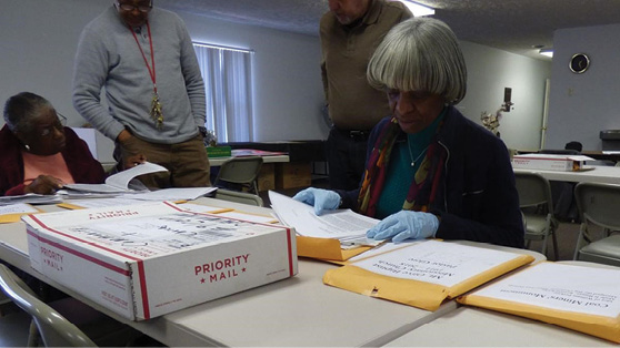 Project Team member, Pamela Smoot, SIUC Department of History, reviews papers at community event held in Colp, Illinois, 2018.  Image courtesy of Mary Halstead.
